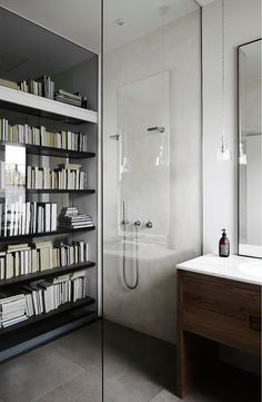 How cool would it be to have a double sided mirror in an unexpected place.  Behind a book shelf what a great idea.