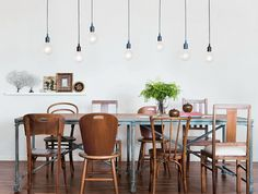 Multiple simple bare bulb pendants over dining table. I love chandeliers, but this is pretty great too.