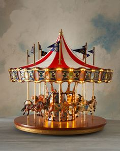 This is a true collector's piece, a oversized carousel. It features a classic peaked fabric roof and a wooden base and is festooned with flags that move up and down with the hand-painted animals. It has Illuminated facade panels. The musical light show with hundreds of miniature LEDs. It plays 20 Christmas carols  the name of this piece is the Anniversary Carousel. It is at Neiman Marcus.