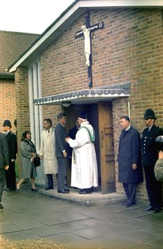 """1963. 30 Juin. By Robert KNUDSEN. KN-C29353. President John F. Kennedy Departs Church in England. President John F. Kennedy shakes hands with Father Charles P. Dolman before entering the Presidential limousine (Lincoln-Mercury Continental) following mass at Our Lady of the Forest Church, Forest Row, England. Also pictured: White House Secret Service agents, Win Lawson (far left), Gerald A. """"Jerry"""" Behn (right of Father Dolman), and Ken Wiesman (holding open car door)."""