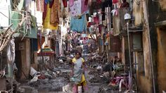 A woman walks in an alley filled with mud and debris to collect relief goods as clothes are hung out to dry after floodwaters receded in Chennai India on December 7 2015