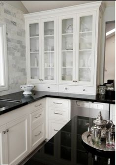 Black counter top with white cabinets & touches of silver & grays~ Love the back splash
