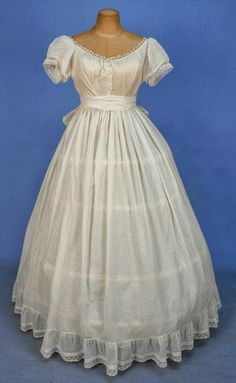 1860s 2-piece white dotted Swiss, boned bodice having short puffed sleeve, front buttons and bobbin lace trim, lined in ivory silk under white cotton, unlined skirt having gathers with ribbon waistband, hem ruffle trimmed with embroidered net band, and self sash. Via Whitaker Auctions.