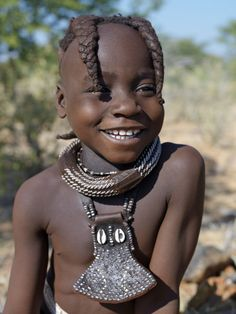 Africa | A young girl, her body lightly smeared with a mixture of red ochre, butterfat and herbs, wears a round white-beaded necklace, called ombwari, a tradition of all Himba people. Her other neck ornament, an eha, is made of leather decorated with metal studs. Her hair is styled in two plaits, which is customary for girls until adolescence. Kaokoland, Namibia | © Nigel Pavitt / John Warburton-Lee