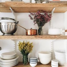 Kitchen utensils displayed on a shelf in between small vases of flowers.