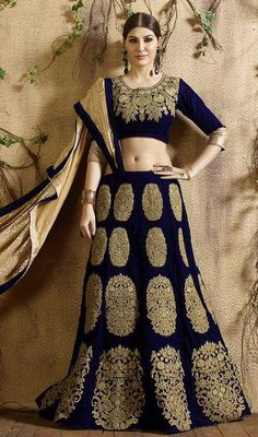 Make understated elegance your signature style as you don this navy blue color velvet embroidered lehenga choli. The lace, stones amd resham work on attire personifies the total look. #velvetlehengacholie #onlineembroideredlehengas #fashionablelookghagaracholi