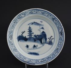 A Ming Porcelain Ko-Sometsuke Dish, Transitional Period, Tianqi to Chongzhen c.1625-1640. The Scene on this Small Blue and White Dish Perhaps Depicts the Immortal Laozi. The Design Shows a Town with a Pagoda and a Large Banner, the Buildings are Enclosed Between Crenellated Walls with a Large Fortified Gate. In the Foreground is a Figure, Perhaps Laozi, the Immortal who founded Daoism, he is on a Horse with His Servant Processing Along a Path to the Gate.