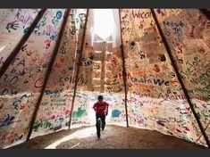 Jesse Jaso, 12 ans, entre dans le tipi de l'Unité, au camp de la pierre sacrée, le 11 septembre 2016. Le tipi est signé par des manifestants de toute l'Amérique du Nord et du monde. Pendant près de 10 mois, des membres de la tribu des Sioux de Standing Rock et leurs alliés ont campé en opposition au pipeline Dakota Access qui traverse leur territoire et menace leur approvisionnement en eau. Amber Bracken/ PRESS PHOTO