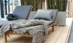 concrete planters (filled with branches perhaps?) and contemporary sun loungers on a pale wooden deck (fabulous chunky knit throw)