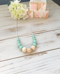 This mint nursing necklace will keep your little one entertained for hours- a great distraction for those restless, inquisitive and curious babies while feeding!  This environmentally friendly necklace is made from 100% food-grade silicone beads and natural untreated eco wood. The necklace is complete with a strong 60cm satin nylon cord and features a safety breakaway clasp, designed to pop open when pulled and tugged on. Turquoise Necklace, Beaded Necklace, Necklaces, Nursing Necklace, Mint, New Mums, Teething, Food Grade, Cord