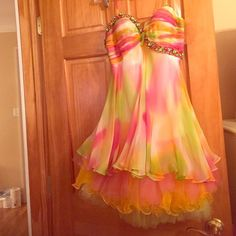 Pink,orange,lime green cocktail dress with beading Pink,orange,lime green cocktail dress with beading on top and rouching on bust. Great for prom or for a formal event. The dress is strapless but comes with detachable straps as shown in the pic the dress is in mint condition no stones missing or anything except there's on little pull on the top layer as shown it is not visible when worn due to the skirt having many different layers ! Cups are tacked in but can be cut right off. Dress is by…