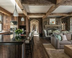 Example of a large rustic mountain style u-shaped open concept cabin kitchen design in Jackson with an island, a double-bowl sink, flat-panel cabinets, dark wood cabinets, dark hardwood floors, solid surface countertops, brown backsplash and stainless steel appliances