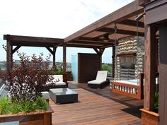 Set under pergolas for shade, this contemporary outdoor deck is a getaway in the city. Comfortable seating areas, from the bed swing to the contemporary sofas and lounge chairs, all center around the stacked stone fireplace.