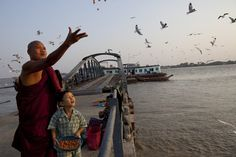 A Burmese monk and his son feed the seagulls on a jetty along the Yangon river ahead of the parliamentary elections March 29, in Yangon, Myanmar. The upcoming vote is seen as an important vote of confidence for the country as it continues on the road to political and diplomatic reform.   PAULA BRONSTEIN - G...
