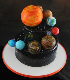 Two tier cake covered in fondant with 3D handmade planets floating around.  www.butterflybakeshop.com/