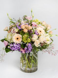Pastel Gathering A wonderful, medium lush, garden style arrangement of all pastel flowers including roses, lyssianthus and gerbers in shades of cream, soft pink and lavender.  #robertsonsflowers