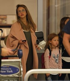 So fly! Jessica Alba covered up her growing bump in a grey jumpsuit as she left the transport hub alongside her two daughters, Haven and Honor