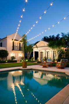 Strands of outdoor lights cross over the pool in this traditional backyard, giving the space an ethereal quality and inviting nights of outdoor entertaining. A cozy conversation area includes plush seating and a table that does double-duty for dining or cocktails.