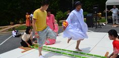 """A religious sister dances the """"tinikling"""" traditional dance from the Philippines. The tinikling dance is one of the most popular and well-known of traditional Philippine dances. It involves two people beating, tapping and sliding bamboo poles on the ground and against each other in coordination with one or more dancers who step over and in between the poles in a dance."""