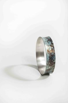 By Alistair McCallum. Mokume Gane Bangle made from 7 layers of silver copper and gilding metal.