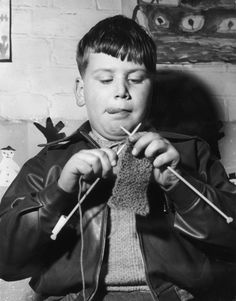 """"""" Tongue out in concentration David """"Buster"""" Burton aged 10 finds knitting a lot harder than he thought it would be. He is one of three boys learning to knit during the hobbies instruction class at Port Vale County Primary School, Hertford. © Derek..."""