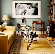 A yellow couch is paired with a glass coffee table, a brown chair, brown shelving, multicolor rug and antique looking lamp