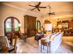 9150 The Lane, Naples, FL 34109 | Family room with a wet bar - open to the kitchen - great for entertaining.  Double wood arched doors to the side garden terrace.  Quail Woods Estates