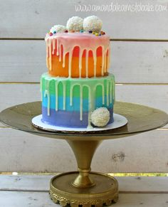 Rainbow drip cake! A two-tier mini drip cake with horizontal buttercream stripes, white chocolate ganache, raffaello truffles, and Wilton sprinkles. Visit website to learn how to decorate!