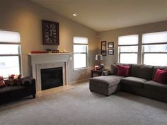 The light-filled great room has large windows, a gas fireplace with marble surround mantle, and plant shelf.