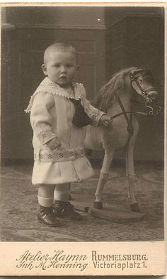 "'Unbreeched"" boy  in dress. Babies (girls and boys) were clothed in dresses until they were toilet trained OR ready to be apprenticed or go to work. Unbreeched meant 'not wearing trousers'. Pferdchen by Minna1903, via Flickr"