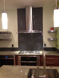 Glass backsplash detail and open wall shelving. Designed by Kitchen Planners in Rockville, MD