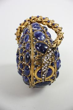 Stunning handbag from Iradj Moini is made of gold-toned metal that is set with clear faceted rhinestones and lapis lazuli cabochons of varying sizes. Snake ...