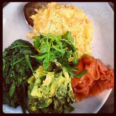balanced gourmet brunch of sourdough toast, scrambled egg, spinach, smashed avocado and smoked salmon
