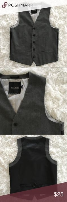 """MENS Topman gray and black vest This Topman best features side slits, a buckle in the back, and striped lining. The front is gray and the back is black. Wear with a button down shirt for a classic look or with a graphic tee for something more casual. Size 38, in excellent used condition. Length is 23.5"""" at the longest point in front. Initials have been written on the tag inside, as pictured, and vest is priced to reflect that.   Feel free to ask me any questions, make an offer, or bundle for…"""
