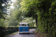 A documentary photograph of a bride and groom traveling to their vintage inspired New England wedding in a blue Volkswagen Bus Gina Brocker Photography