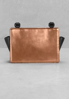 This structured leather bag is detailed with a bronze metallic panel and features a long shoulder strap for hands-free comfort.
