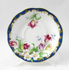 Vintage bone china tea cup and saucer, white and blue with colourful flowers. Narcissus is the name of the pattern. Excellent condition (see photos). Markings read: Narcissus Fine Bone Bell China England Please bear in mind that these are vintage items and there may be small