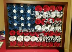 Paper flower American Flag in an 11x24 shadow box.   69 flowers in all. With vinyl lettering on glass.