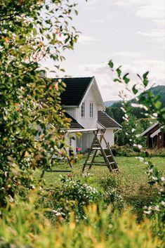 I dette romantiske huset føres gamle tradisjoner videre - tro mot den klassiske byggestilens særpreg. Huset er satt opp i 1986, men er tegnet og bygget i en stil som gjør at det ser eldre ut og passer inn i et gårdsmiljø. Det landlige huset er kledd med tidsriktig lektekledning og har klassisk listverk rundt vinduene. Cabin, House Styles, Home Decor, Decoration Home, Room Decor, Cabins, Cottage, Home Interior Design, Wooden Houses