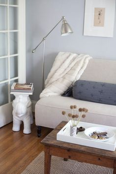 I need a reading lamp like this, plus I love how the white tray looks against the rough wood coffee table.