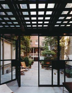 Garden Pavilion, NYC  Photo: David Allee Custom steel bi-folding doors, glass bock ceiling with steel frame, Hans Wegner teak rope-seat chairs, Piero Fornasetti table.