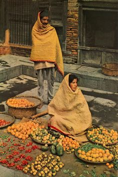 National Geographic, March 1960 | Katmandu Fruit Vendors Break Winter's Chill With Cotton Quilts | Sidewalk market displays tangerines, guavas, tiny bananas, cashew, papaya (center), peas, and limes. Most of the capital's fruit must be imported from beyond the Katmandu Valley. (Kodachrome by Schuyler Jones) p. 381