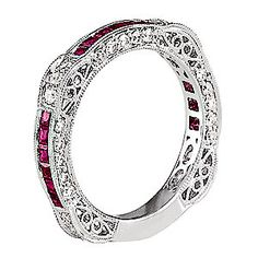 this beautiful ruby and diamond band is shown in 18 karat white gold with an intricate design along the shank