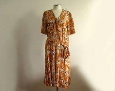 1920s silk dress in a floral print of orange hues with white and black.