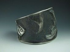 Sterling silver repousse cuff bracelet with goldfish swimming around it. At www.nrwoart.com