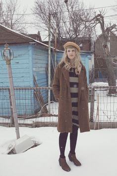 long coat, subtle neutral colors against thick black stripes. beret and booties add some charm to the outfit.