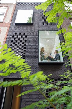 Large glass window boxes alternate with the use of brick facade screens, which allow for ventilation while providing privacy and security. The home of architects Gwendolyn Huisman and Marijn Boterman, in Rotterdam.