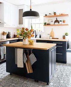 She created a two-tone color palette for her modern kitchen makeover. Then, she added open shelving, butcher block countertops, a patterned tile floor, and a bright white tile backsplash to tie her new style together. Paint Kitchen Cabinets Like A Pro, Navy Kitchen Cabinets, Kitchen Cabinet Colors, Kitchen Paint, Home Decor Kitchen, New Kitchen, Home Kitchens, Blue Cabinets, Small Kitchens