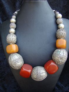 by Nancy Sathre-Vogel.  | Necklace; 5 large old Ethiopian silver beads are combined with two colours of African 'Amber beads'. | The Ethiopian silver beads are all signed, and like most old silver beads {ca. 50 - 70% silver content} from Ethiopia, these were made by melting down other silver ornaments and Maria Theresa Thaler coins.  The amber beads are copal.