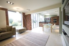 Family room with seating, built in TV, dining and kitchen by chadwickdryerclarke